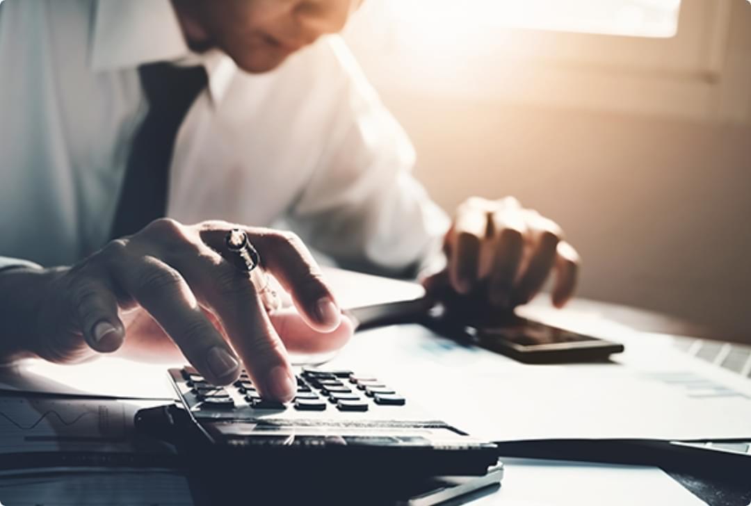 man at desk using calculator
