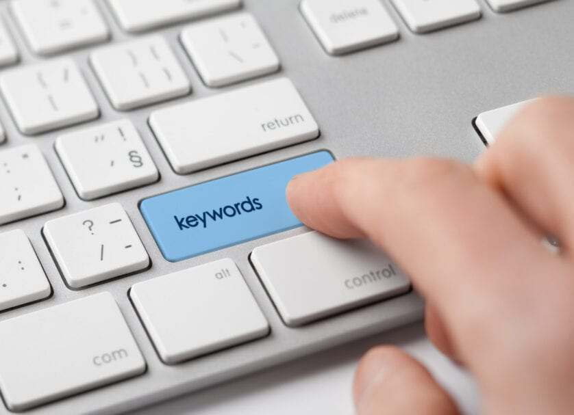 finger touching keywords button on keyboard