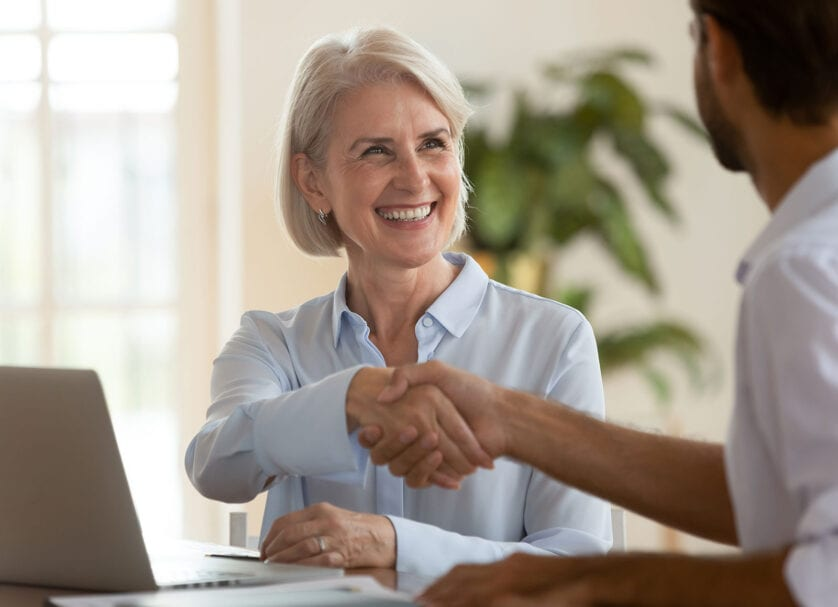 seated woman shaking hands with SEO partner